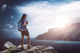 Hiker standing on a rock overlooking sea and coast
