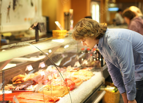 Man shopping for fresh fish seafood in supermarket retail store