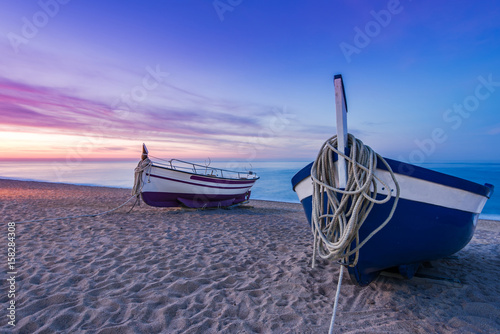 Foto op Canvas Caraïben Fishing boat on sandy beach at nostalgic sunrise
