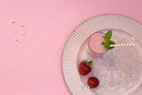 Erdbeere Milchshake in Gläsern mit Strohalmen auf einem mit Ornamenten verzierten Tablett auf pink farbigem Hintergrund
