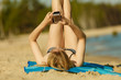 Woman in bikini sunbathing and relaxing on beach