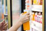 woman's hand open convenience store refrigerator shelves and pick product - 158326350