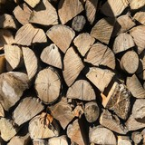 Pile of firewood. Stack of chopped tree logs nature background texture. Firewood stacked. Chipped organic firewood. Organic Background