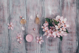 Creative beauty concept cosmetics, perfume and petals of a blossoming apple tree  Flat lay.