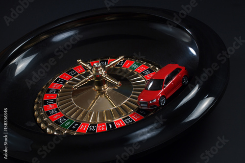 Red toy car on the roulette wheel плакат