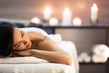Beautiful girl in spa salon on candle background