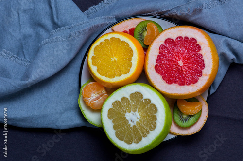 sliced fruit of the citrus on a plate on gray blue towel black background