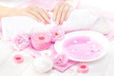beautiful pink manicure with tea rose on the white wooden table. spa