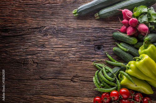 Vegetable.Fresh vegetable tomato radish green pepper peas zucchini and cucumber on rustic oak table.