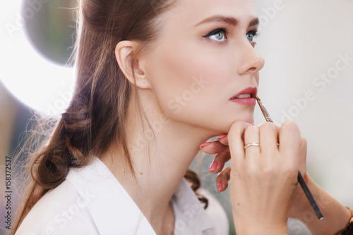 Closeup of female makeup artist paint her lips by cosmetic brush lipstick Poster
