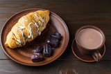 Hot chocolate or cocoa drink in cup and sweet croissant and dates fruit at plate on dark brown wooden table