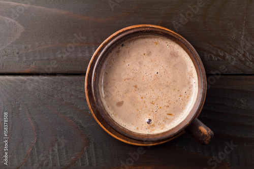 Hot chocolate or cocoa drink in clay cup, on dark brown wooden table, top view