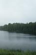 misty morning on scandinavian lake with rain ripples on water, summer season