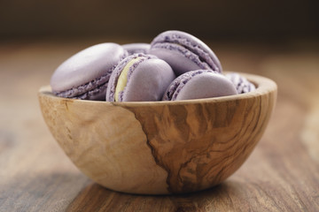 violet macarons in wood bowl on wooden table, closeup