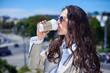 Wonderful woman enjoying city panorama and drinking coffee