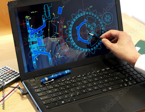 engineer working on computer at the design of mechanical piece