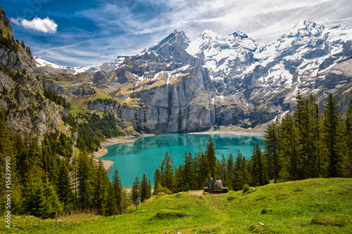 Amazing tourquise Oeschinnensee with waterfalls, wooden chalet and Swiss Alps, Berner Oberland, Switzerland. - 158399910
