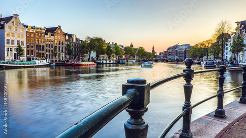 The most famous canals and embankments of Amsterdam city during sunset. General view of the cityscape and traditional Netherlands architecture.
