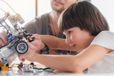 Fototapeta Concentrated male kid repairing technical toy