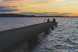 Unrecognizable people relaxing on lake pier during beautiful sunset