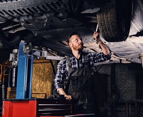 Mechanic balancing car's wheel in a workshop. - 158439754