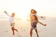 Happy kids running on beach in evening