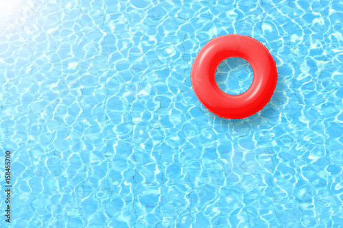 Foto Murales red swimming pool ring float in blue water and sun bright. concept color summer.