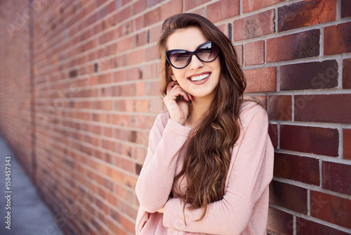 Beautiful young woman smiling standing on city street