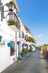 Walkway with flower pots on the wall in the white village of Mijas, Costa del Sol, Andalusia, Spain