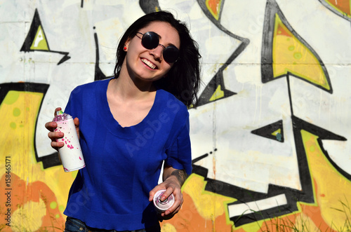Portrait of an emotional young girl with black hair and piercings. Photo of a girl with aerosol paint cans in hands on a graffiti wall background. The concept of street art and use of aerosol paints