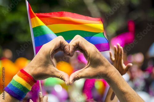 Poster Supporting hands make heart sign and wave in front of a rainbow flag flying on t