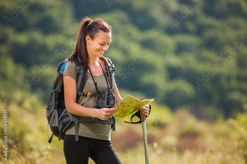 Young woman is hiking in mountain and enjoying nature. She is looking at map.