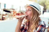 Cheerful young woman enjoying slice of pizza