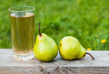 A glass of juice and pears on a wooden background. The concept of harvesting