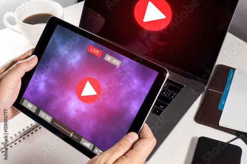 Man Hand Holding Tablet with Live Streaming with Modern laptop computer Poster