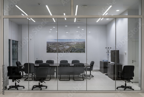 A modern meeting room with transparent partitions, with a large table and comfortable office chairs.