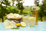 Two glasses of elderflower lemonade and bottle of homemade syrup