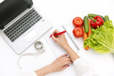 Fototapety Vegetable diet nutrition or medicaments concept. Doctors hands writing diet plan, ripe vegetable composition, laptop and measuring tape on white background