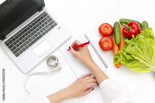 Vegetable diet nutrition or medicaments concept. Doctors hands writing diet plan, ripe vegetable composition, laptop and measuring tape on white background