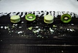 Green macaroons and kiwi as a border on a wood background with white tablecloth