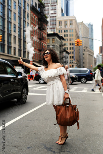 Poster Beautiful woman stops a taxi in new York