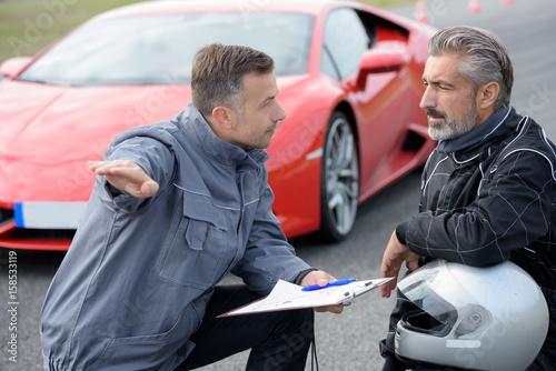 Men in discussion, sports car in background - 158533119