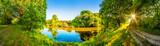 Landschaft im Sommer mit Fluss, Sonne, Weg und Wald - 158535722