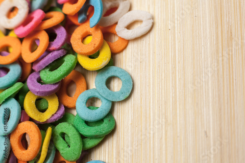 Multi colored sweet sugar circle pattern on wooden background Poster