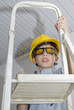 Boy with helmet and hammer on stepladder