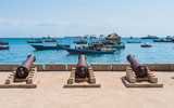 embankment with guns in Zanzibar Stone Town with boats in ocean and sky on the background