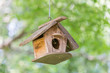 The wooden small birdhouse hanging on tree with blurred natural green garden in background.