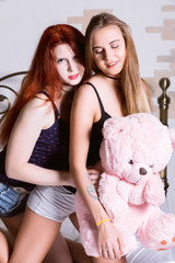 Two girlfriends huging and kissing on a bed in bright bedroom. Lesbian couple with teddy bear