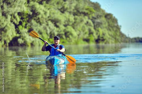 Poster  Man paddling a kayak on summer day.