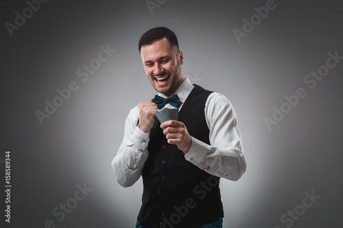Young man in shirt and waistcoat watch his poker cards, studio shot плакат